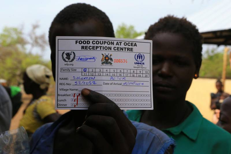 South Sudanese refugee displaced by fighting uses his meal card to cover his face as he waits to be served porridge on arrive at Imvepi settlement in Arua district, northern Uganda, April 4, 2017. Picture taken April 4, 2017. REUTERS/James Akena