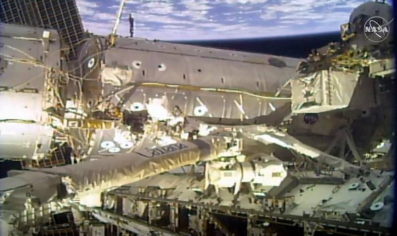 """This NASA TV video frame grab shows Astronauts Mike Hopkins and Victor Glover, Jr.(C) as they finish a four-year effort to upgrade the International Space Station's power system during a spacewalk on February 1, 2021. - Astronauts Mike Hopkins and Victor Glover are conducting a spacewalk Monday to finish battery upgrades and install high-definition cameras outside of the International Space Station. This is the second spacewalk for the duo in just a matter of days. (Photo by Handout / NASA TV / AFP) / RESTRICTED TO EDITORIAL USE - MANDATORY CREDIT """"AFP PHOTO /NASA TV/HANDOUT """" - NO MARKETING - NO ADVERTISING CAMPAIGNS - DISTRIBUTED AS A SERVICE TO CLIENTS"""