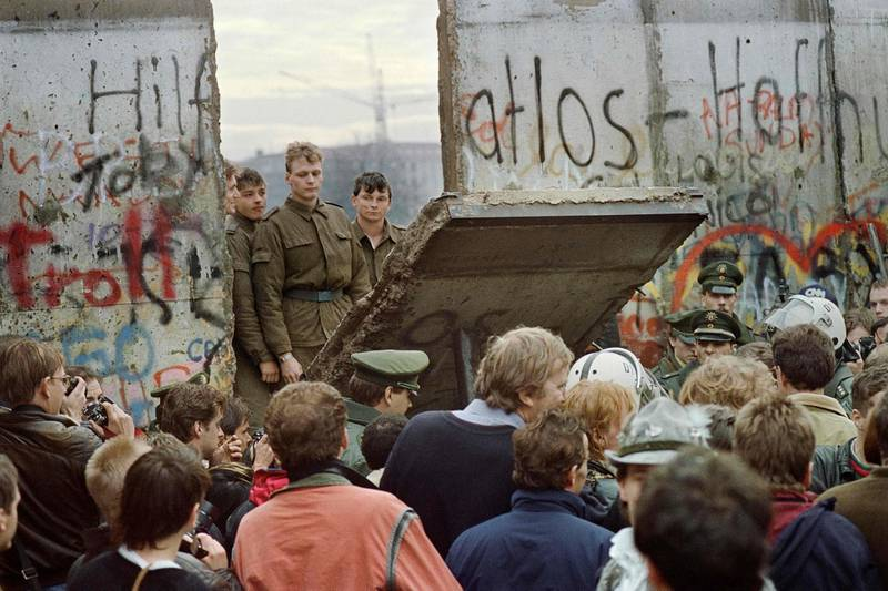 (FILES) This file photo taken on November 11, 1989 shows West Berliners who are crowded in front of the Berlin Wall early 11 November 1989 as they watch East German border guards demolishing a section of the wall in order to open a new crossing point between East and West Berlin, near the Potsdamer Square. The Iron Curtain was at first an ideological and then a physical separation of communist Eastern Europe from the West from the 1940s after World War II. / AFP / GERARD MALIE