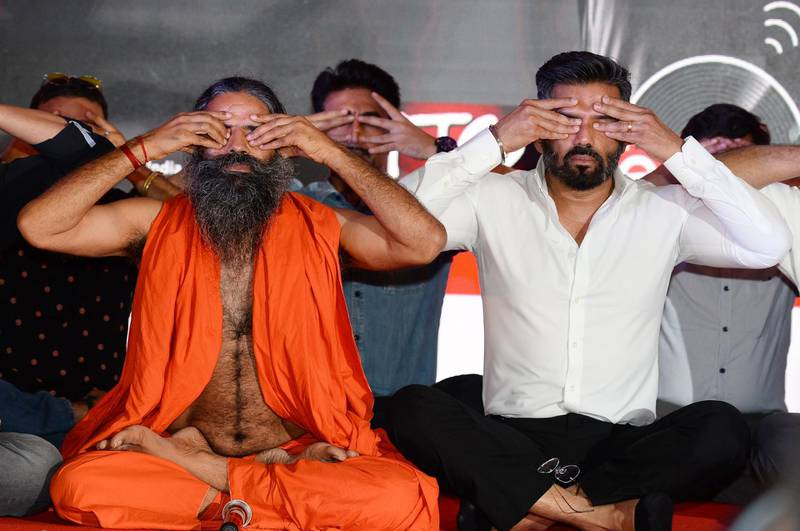 Indian Bollywood actor Suniel Shetty (R) and yoga guru Baba Ramdev perform excercises during a promotional event in New Delhi on June 4, 2018. The yoga guru is starting a country-wide fitness campaign. / AFP / Sajjad HUSSAIN