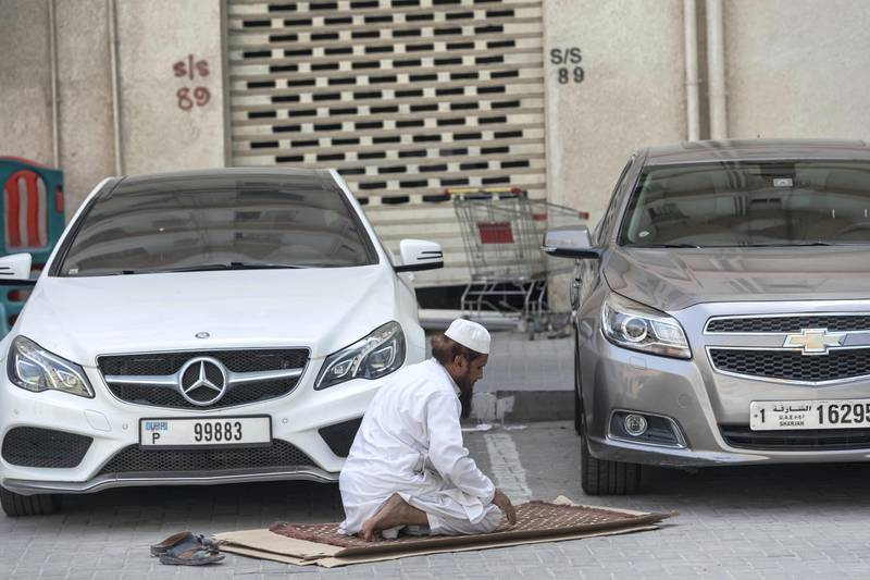 SHARJAH, UNITED ARAB EMIRATES. 04 APRIL 2020. COVID-19 Coverage. General image for gallery and related article. A man prays alone in a parkinglot in Sharjah. (Photo: Antonie Robertson/The National) Journalist: Standalone. Section: National.