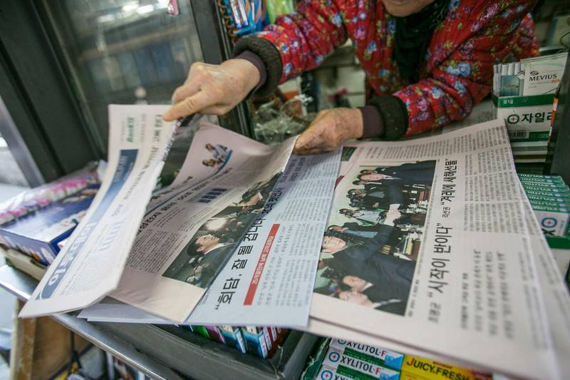 A vendor sorts through newspapers featuring photographs of Cho Myoung-gyon, South Korea's unification minister, left, shaking hands with Ri Son Gwon, chairman of North Korea's Committee for the Peaceful Reunification of the Fatherland,on the front page at a kiosk in Seoul, South Korea, on Tuesday, Jan. 9, 2018. North Korea said it would send a high-level delegation to the Winter Olympics in South Korea next month while expressing a desire to resolve issues on the divided peninsula through dialogue and negotiations. Photographer: Jean Chung/Bloomberg