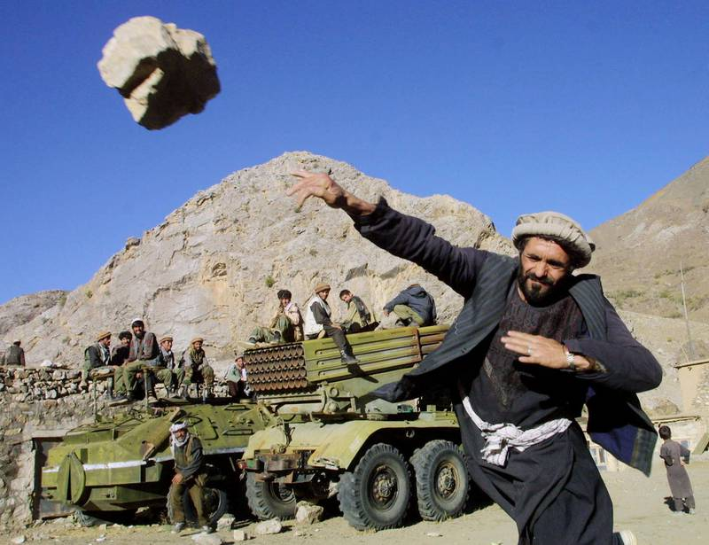 395753 02: A Northern Alliance fighter throwing rocks as part of a popular national game yards away from a multiple Grad missile launcher October 12, 2001 in the Salang Gorge in Northern Afghanistan. (Photo by Oleg Nikishin/Getty Images)