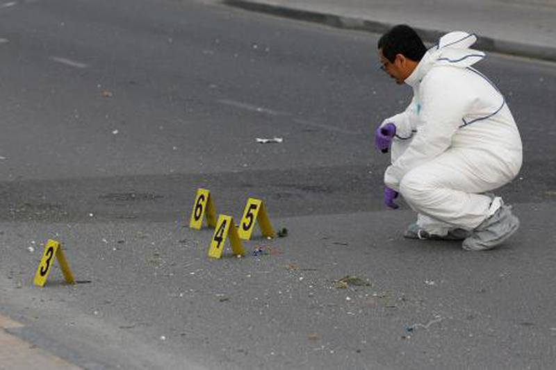 A police officer with the explosive unit investigates the scene of an explosion in the village of Sanabis, west of Manama, January 30, 2013. A home-made bomb exploded near a police check point, injuring three police officers and two civilians, according to the police at the site. REUTERS/Hamad I Mohammed (BAHRAIN - Tags: POLITICS CIVIL UNREST) *** Local Caption ***  BAH05D_BAHRAIN-PROT_0130_11.JPG