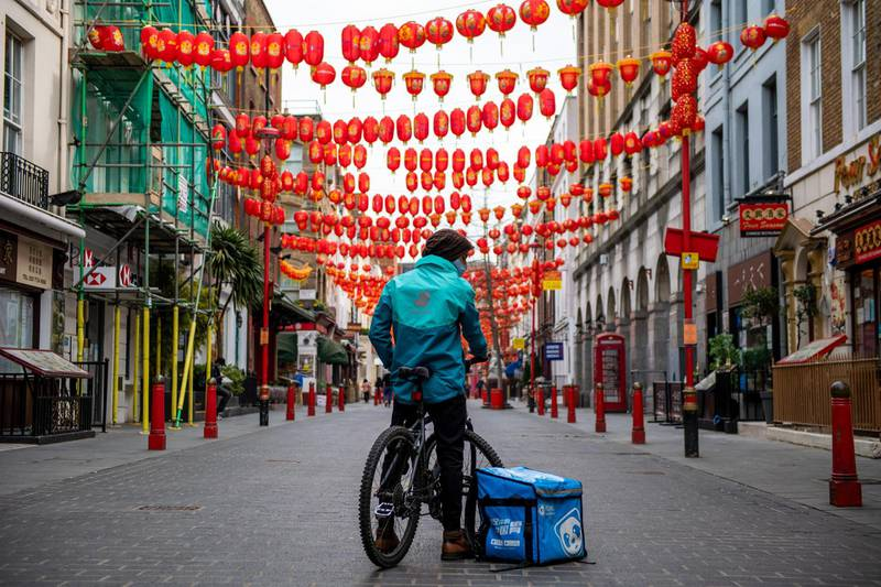 A food delivery courier wearing a Deliveroo Holdings Plc jacket and a bag from the Hungry Panda Ltd. food delivery service waits for orders in Chinatown in London, U.K., on Wednesday, March 31, 2021. Food-delivery startup Deliveroo Holdings Plc sank as much as 31% in its London debut after its initial public offering raised 1.5 billion pounds ($2.1 billion), putting pressure on the Citys efforts to boost its profile as a technology and listings hub post-Brexit. Photographer: Chris J. Ratcliffe/Bloomberg