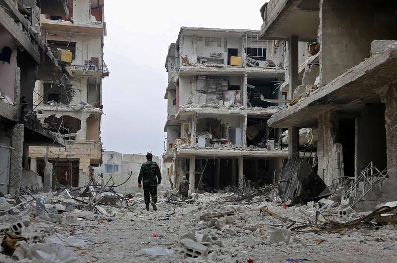 TOPSHOT - Syrian government soldiers walk down a street past destroyed buildings in the town of Hazzeh in Eastern Ghouta, on the outskirts of the Syrian capital Damascus, on March 28, 2018. / AFP PHOTO / STRINGER