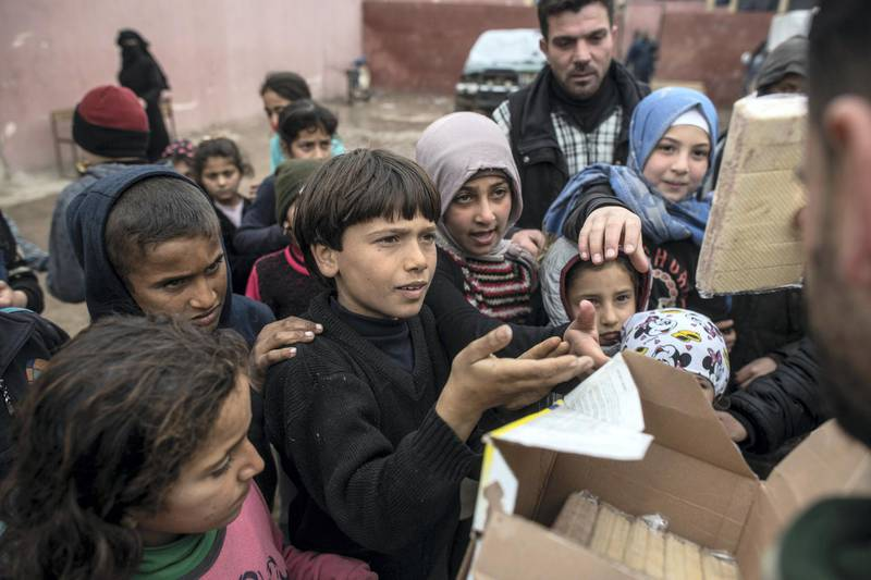 """IDLIB, SYRIA - FEBRUARY 21: Displaced Syrian children gather to receive humanitarian aid supplied by an NGO on February 21, 2020 in Idlib, Syria. Turkey's President Recep Tayyip Erdogan in a speech Tuesday threatened, """"imminent operations in Syria's Idlib if Damascus fails to withdraw behind Turkish positions"""" The threat comes after Syria's government and its ally Russia rejected demands to pull back to ceasefire lines agreed upon in the 2018 Sochi accord. More than 900,000 civilians have been displaced by fighting in or around Idlib since December 1. Idlib is the last rebel stronghold of fighters trying to overthrow Syrian President Bashar al-Assad and in the past years has become the last safe haven for civilians displaced by fighting in other areas of Syria, its population has doubled to close to three million people, many of whom are now fleeing the government offensive towards overcrowded camps close to the Turkish border amid freezing conditions, creating a humanitarian disaster. (Photo by Burak Kara/Getty Images)"""