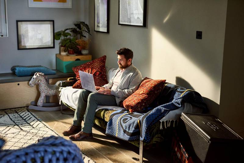 Portrait of man on sofa using laptop in living room, small business, online, industrious, efficiency