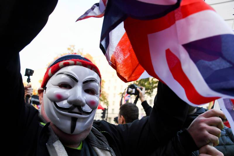 A Pro Brexit demonstrator wearing a Guy Fawkes mask, protests outside the gates of Downing Street in London, Thursday, Oct. 31, 2019. The EU has allowed Britain to delay its Brexit departure from the bloc until Jan. 31, enabling Britain to hold a general election on Dec. 12. (AP Photo/Alberto Pezzali)