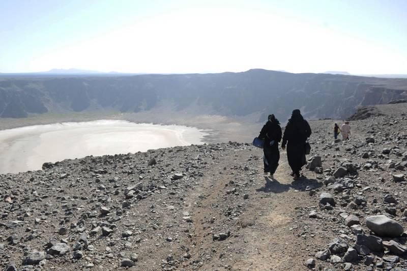 Saudi women walk through the Al-Wahbah volcanic crater in the Al-Wahbah desert, some 360 kms northeast of Jeddah, on November 17, 2017. / AFP PHOTO / AMER HILABI