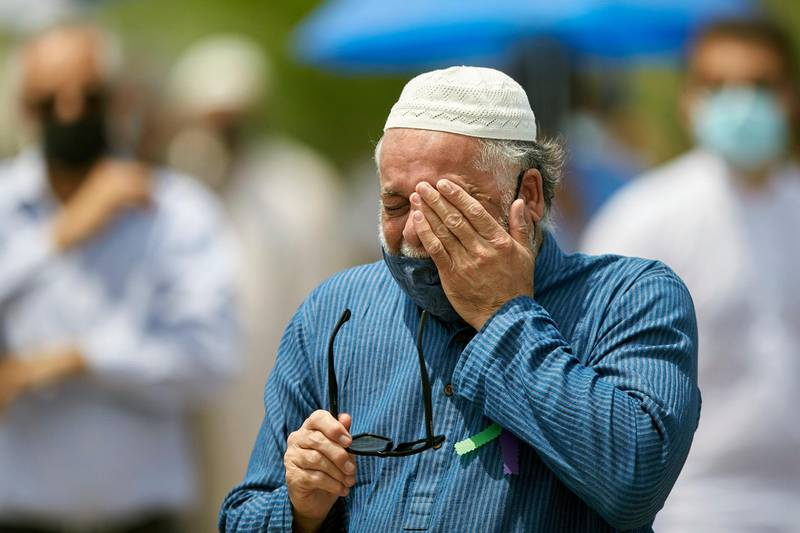 A man wipes away a tear during the funeral service for the victims of the deadly vehicle attack on five members of the Canadian Muslim community in London, Ontario, Saturday, June 12, 2021. Four members of the family died and one is in critical but stable condition. A 20-year-old male is in custody and has been charged in what police say is a motivated hate crime.  (Geoff Robins/The Canadian Press via AP)