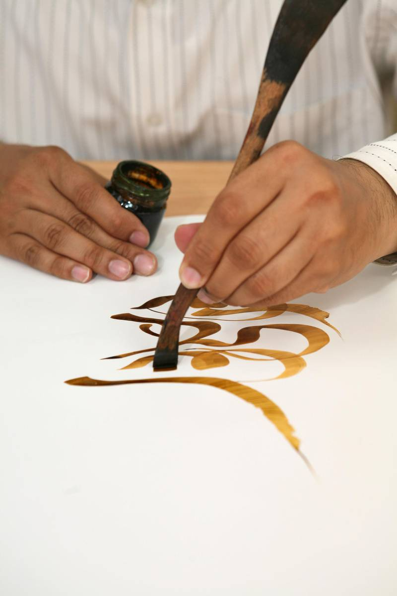 DUBAI, UNITED ARAB EMIRATES - April 8: Khaled Al-Saai'i, Arabic calligrapher and painter, giving a calligraphy demonstration in the Calligraphers' Studio at the Sharjah Museum for the Art of Arabic Calligraphy, in Sharjah on April 8, 2008. (Randi Sokoloff / The National)