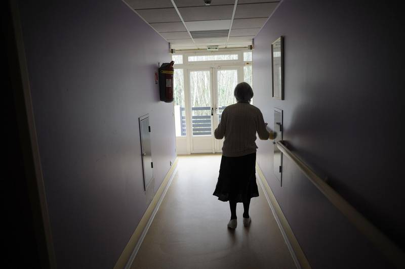 """(FILES) In this file photo taken on March 18, 2011 a woman, suffering from Alzheimer's desease, walks in a corridor in a retirement house in Angervilliers, eastern France.    Construction has started on May 30, 2018 on the first """"Alzheimer village"""" near Dax, France, the second in Europe, where new forms of medical support will be experimented.  / AFP / SEBASTIEN BOZON"""