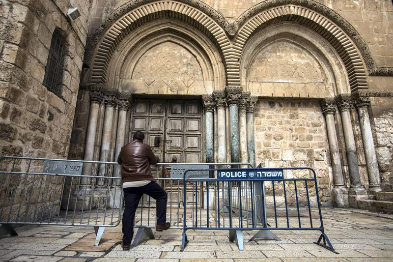 A Christian pilgrim waits outside the barrier of the closed Church of the Holy Sepulchre in the Old City of Jerusalem on Monday February 26,2018.The Church of the Holy Sepulchre  remained closed for a second day after church leaders in Jerusalem closed it to protest against Israeli's announced plans by the cityÕs municipality earlier this month to collect property tax (arnona) from church-owned properties on which there are no houses of worship. (Photo by Heidi Levine for The National).