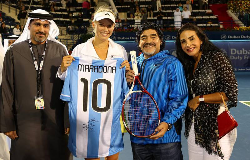 DUBAI, UNITED ARAB EMIRATES - FEBRUARY 21:  Caroline Wozniacki of Denmark exchanges gifts with football legend Diego Maradona as they pose for a picture with Salah Tahlak, Tournament Director during day four of the WTA Dubai Duty Free Tennis Championship on February 21, 2013 in Dubai, United Arab Emirates.  (Photo by Julian Finney/Getty Images) *** Local Caption ***  162265798.jpg