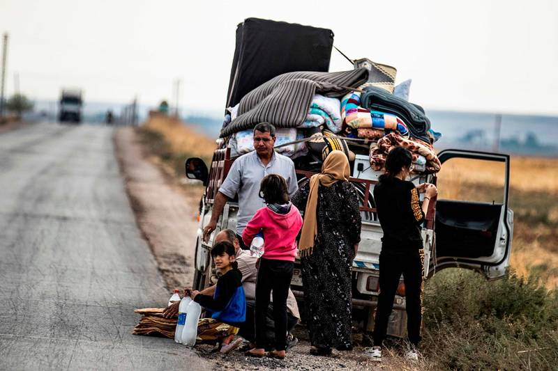 """TOPSHOT - Syrian Kurdish and Arab families are pictured fleeing in the countryside of the town of Darbasiyah, on the border between Syria and Turkey, towards the town of Hassakeh on October 22, 2019. Syria's Kurds have withdrawn all their forces from a strip of land bordering Turkey in compliance with a US-brokered truce deal to stem a Turkish assault, a top Kurdish official said. """"We have fully complied with the conditions of the ceasefire agreement,"""" Redur Khalil told AFP just hours before a deadline. """"We have withdrawn all our military and security forces from the area of military operations from Ras al-Ain in the east to Tal Abyad in the west,"""" he said.  / AFP / Delil SOULEIMAN"""