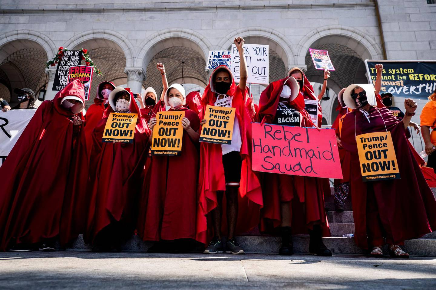 epa08754341 Protesters wearing handmaid costumes stands in front of City Hall as they join hundreds of protesters during a pre-election Women's march in Los Angeles, California, USA, 17 October 2020. The second Women's March of 2020 was organized to encourage women to vote in the upcoming 03 November presidential election, as well as calling on Congress to suspend the confirmation process of the Supreme Court Nominee Amy Coney Barrett.  EPA/ETIENNE LAURENT