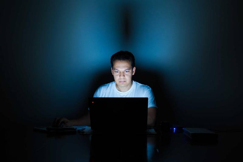 Portrait Of Young Man Using Laptop In Dark Room. Getty Images