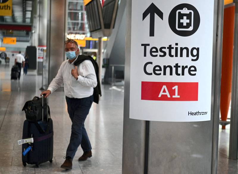 """A passenger walks past signage displaying the way to a Covid-19 test centre, in Terminal 5 at Heathrow airport in London, on June 3, 2021. Health Secretary Matt Hancock has said it remains """"too early"""" to say whether all coronavirus restrictions can end on June 21.  Speaking ahead of a G7 health ministers' meeting, he told reporters: """"It's too early to say what the decision will be about step four of the road map, which is scheduled to be no earlier than June 21.   / AFP / DANIEL LEAL-OLIVAS"""