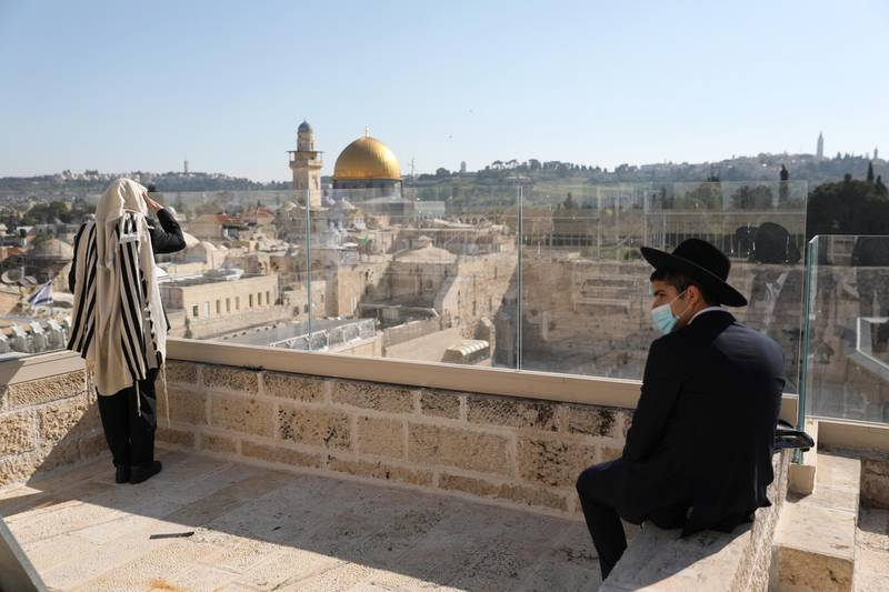 epa08358267 Orthodox Jews pray and keep distance from each other while wearing a protective face mask as they recite the Priestly Blessing on the high holiday of Passover on a rooftop in front of the Western Wall, in Jerusalem, Israel, 12 April 2020. Media reports state, that according to government decision, Israeli police have approved a small prayer while enforcing lockdown on several cities and ultra-Orthodox Jewish neighborhoods across the country in order to prevent the spread of the SARS-CoV-2 coronavirus during the holidays season.  EPA/ABIR SULTAN