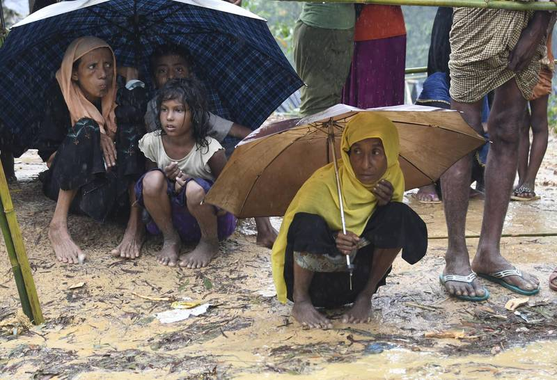 (FILES) In this file photo taken on September 17, 2017 Rohingya refugees protect themselves from rain in Balukhali refugee camp near the Bangladesh town of Gumdhum. Humanitarian agencies have been warning for months about the danger posed by the impending 2018 monsoon, due to start in June, to the welfare of refugees who live cheek by jowl in cramped tents on hillsides, following a mass exodus from Myanmar in 2017.  / AFP PHOTO / DOMINIQUE FAGET