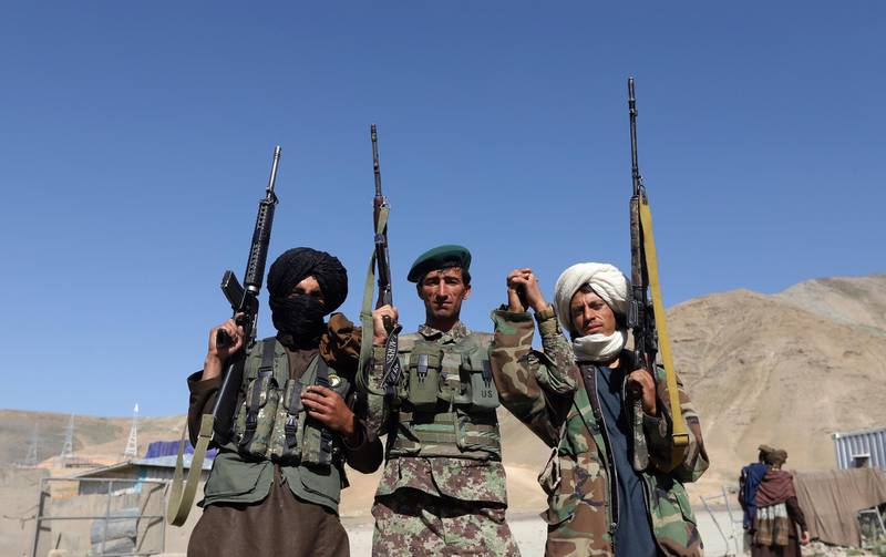 epa06814048 Alleged Taliban fighters and an Afghan national army soldier (C) stand for a photograph during a three-day ceasefire on the second day of Eid al-Fitr, in the outskirt of Kabul, Afghanistan, 16 June 2018. Earlier in the month, President Ghani's government had announced a temporary ceasefire, starting on 12 June, to last until the end of the festival. The Taliban had followed suit a few days later and announced a three-day partial ceasefire during the festival.  EPA/JAWAD JALALI