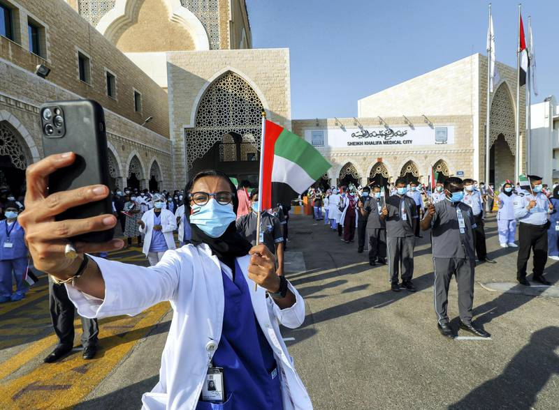 Abu Dhabi, United Arab Emirates, June 21, 2020.    Dr. Fatema Al Kaabi waves the UAE flag during the UAE Air Force's aerobatic display team, Al Fursan,  flies over Sheikh Khalifa Medical City, in an initiative of appreciation by the General Command of the UAE Armed Forces for the nation's medical teams and staff.Victor Besa  / The NationalSection:  NAReporter: