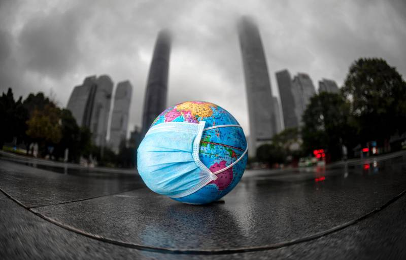 epa08376968 A model of the globe with a face mask left on the ground by the children who were playing with it in Guangzhou, Guangdong province, China, 22 April 2020. World Earth Day is marked in many countries annually on 22 April to raise awareness of environmental protection.  EPA/ALEX PLAVEVSKI