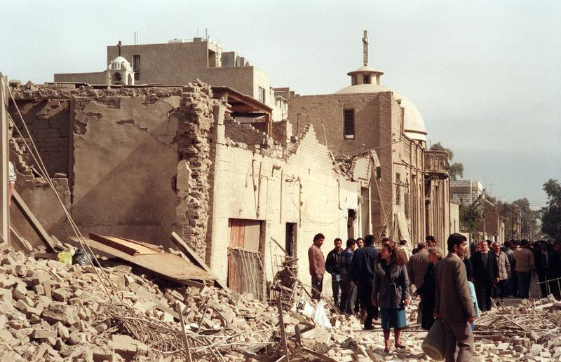 Iraqi civil defence workers and civilians shown in a photo dated 16 February 1991 looking at the damage near a Christian church caused by an allied bombing raid in a Baghdad street. (Photo by STR / AFP FILES / AFP)