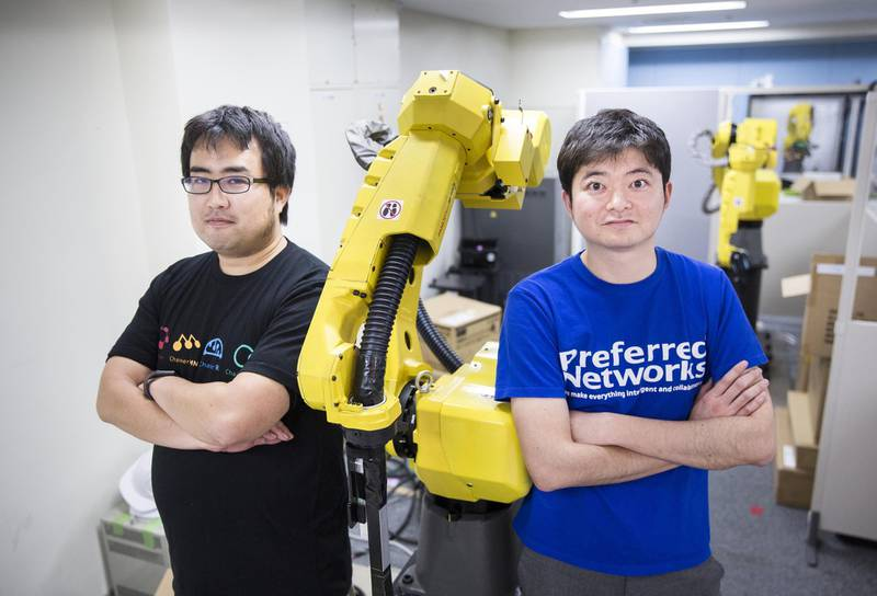Toru Nishikawa, co-founder and chief executive officer of Preferred Networks Inc., right, and Daisuke Okanohara, co-founder and vice president, pose with a Fanuc Corp. robotic arm at their company's headquarters in Tokyo, Japan, on Friday, March 16, 2018. Preferred Networks has only one publicly available product, a whimsical application that uses artificial intelligence to automate the coloring of manga cartoons. Yet the four-year-old firm has become Japan's most valuable startup, with a venture capital funding that priced it at more than $2 billion, according to people familiar with the matter. Photographer: Tomohiro Ohsumi/Bloomberg
