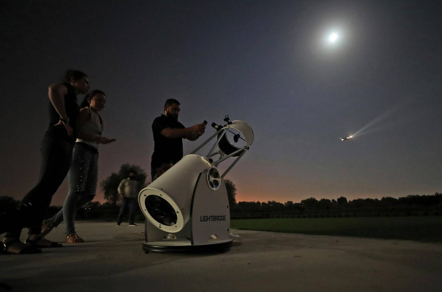 People stand to watch a partial lunar eclipse through a telescope at the Al Thuraya Astronomy Center in Dubai, United Arab Emirates, Tuesday, July 16, 2019. (AP Photo/Kamran Jebreili)