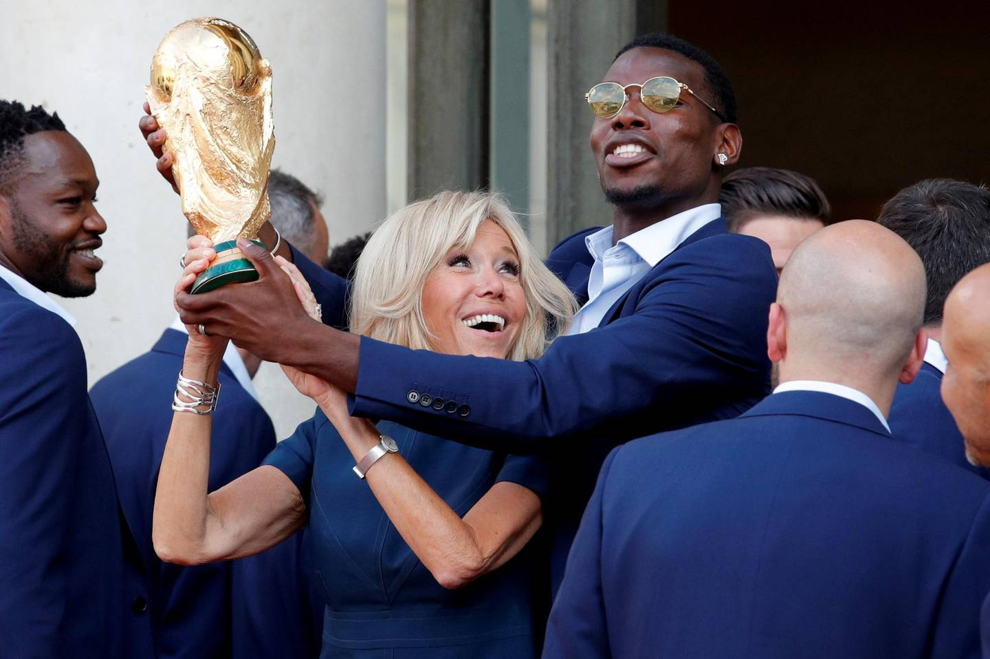 Brigitte Macron, the wife of French President Emmanuel Macron (not pictured), and player Paul Pogba hold the trophy before a reception to honour the France soccer team after their victory in the 2018 Russia Soccer World Cup, at the Elysee Palace in Paris, France, July 16, 2018.   REUTERS/Philippe Wojazer     TPX IMAGES OF THE DAY