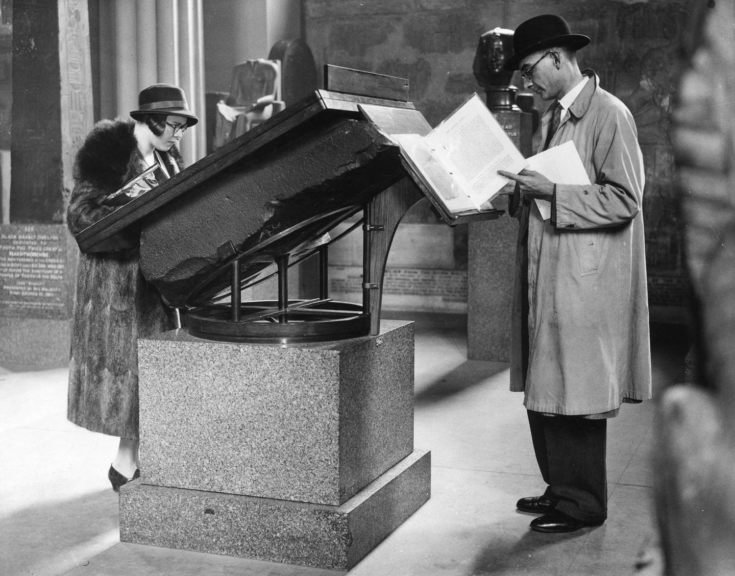 14th September 1932:  Visitors reading information concerning the Rosetta Stone, from the top of the Stone itself, in the Egyptian Gallery at the British Museum.  (Photo by Fox Photos/Getty Images)