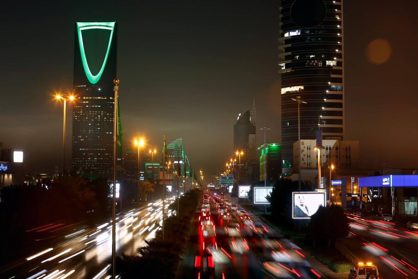 In this picture taken with a slow shutter speed, vehicles pass in front of the landmark Kingdom Tower, at left, as it projects a green light marking Saudi 89th National Day celebrations in Riyadh, Saudi Arabia, late Sunday, Sept. 22, 2019. (AP Photo/Amr Nabil)