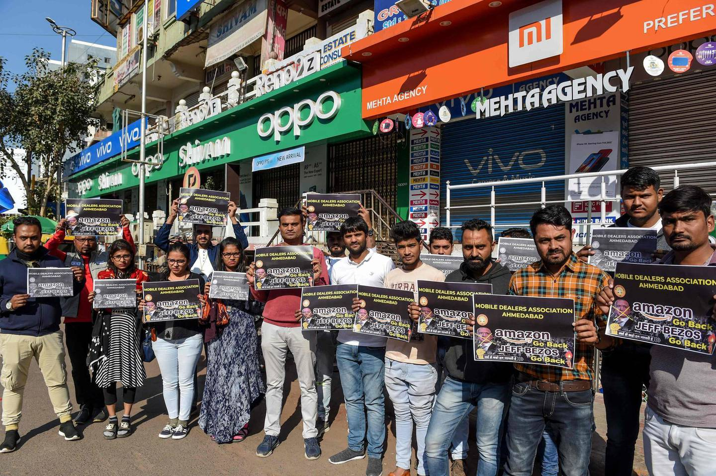 Mobile dealers and members of Ahmedabad Mobile Dealer's Association hold placards as they protest against online shopping platform Amazon outside their closed mobile shops in Ahmedabad on January 15, 2020. Amazon tycoon Jeff Bezos promised on January 15 a new billion-dollar investment in India, just two days after authorities launched an anti-trust investigation into the e-commerce giant.  / AFP / SAM PANTHAKY