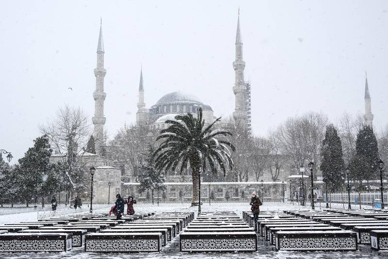 epa08945633 People enjoy their time in front of the Sultanahmet Mosque on a snowy day in Istanbul, Turkey, 18 January 2021.  EPA/SEDAT SUNA