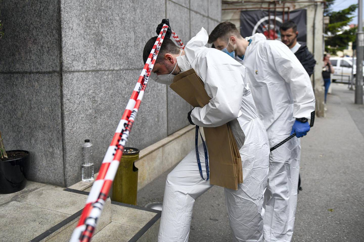 Forensic workers arrive to collect body parts and evidence from a hotel downtown Bucharest, Romania, Friday, June 19, 2020. Gholamreza Mansouri, a former judge from Iran sought by his country to face corruption charges has died after falling from a high floor inside a hotel. Romanian police said only that a man had fallen from a high floor at a hotel in Bucharest, the Romanian capital, and was found dead. (AP Photo/Andreea Alexandru)