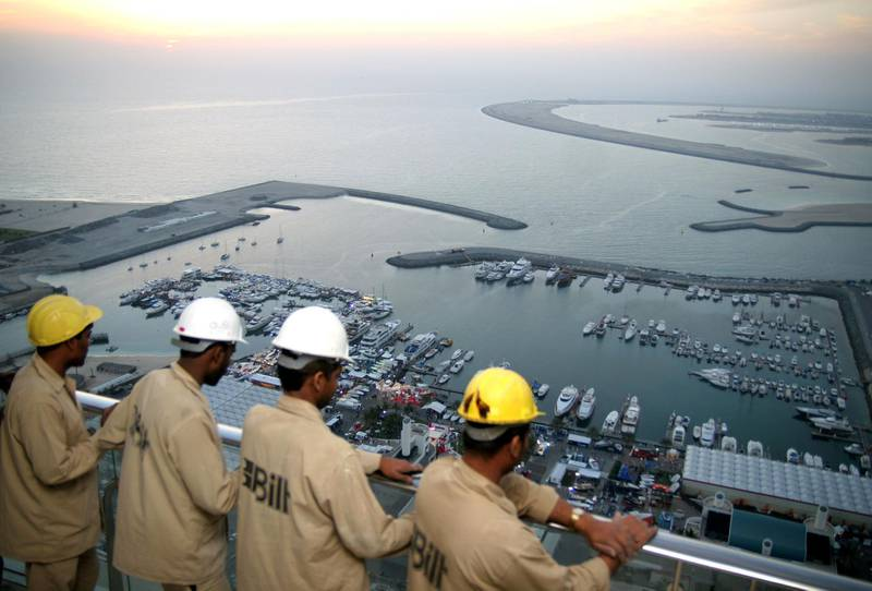 Indian workers watch the openning of Dubai's international boat show from the 50th floor of the tower which is beign constructed behind the Dubai International Marine Club, 14 March 2006. The governor of the UAE central bank sharply criticised yesterday the US Congress opposition to the acquisition of six US ports by Dubai Ports World (DPW) and called for a reassessment of US trade links. AFP PHOTO/ NASSER YOUNES / AFP PHOTO / NASSER YOUNES