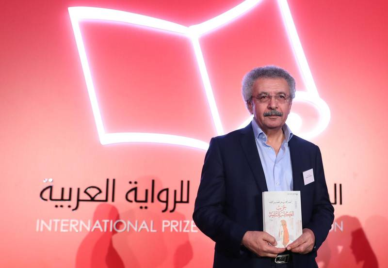 """Palestinian writer Ibrahim Nasrallah poses for a photo after winning the 2018 International Prize for Arabic Fiction for his book titled """"The Second war of the Dog"""" in Abu Dhabi on April 24, 2018. / AFP PHOTO / KARIM SAHIB"""