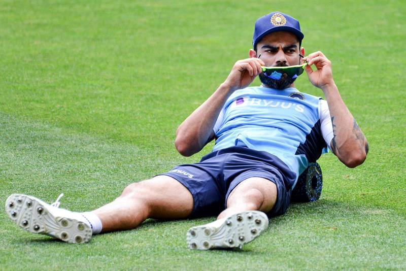 India's captain Virat Kohli does stretching exercises during a training session at Adelaide Oval on December 15, 2020, ahead of the first Test cricket match between Australia and India.   / AFP / Brenton EDWARDS