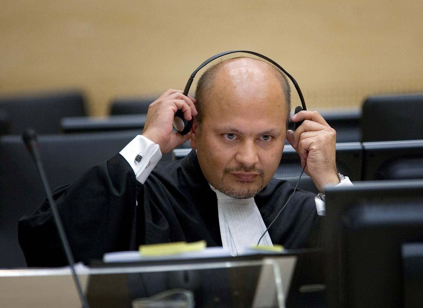 FILE  - In this Monday, June 4, 2007 file photo, lawyer Karim Khan adjust his headphones in the courtroom of the Special Court for Sierra Leone in The Hague, the Netherlands.  Khan is being sworn in Wednesday, June 16, 2021 as the new chief prosecutor of the International Criminal Court, taking leadership of a busy and financially stretched team that is probing alleged atrocities around the globe. Khan, a 51-year-old English lawyer, has years of experience in international lawyer as a prosecutor, investigator and defense attorney. He takes over from Fatou Bensouda of Gambia, whose nine-year term ended Tuesday. (AP Photo/Robert Vos, Pool, File)