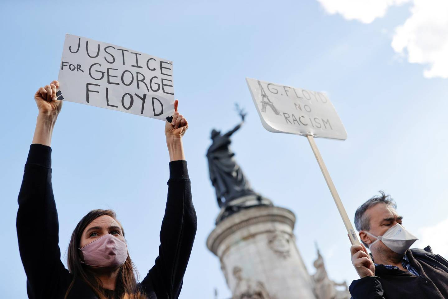 Demonstrators hold placards as they attend a protest at the Place de la Republique square, following the death of George Floyd in Minneapolis police custody, in Paris France, June 9, 2020. REUTERS/Christian Hartmann