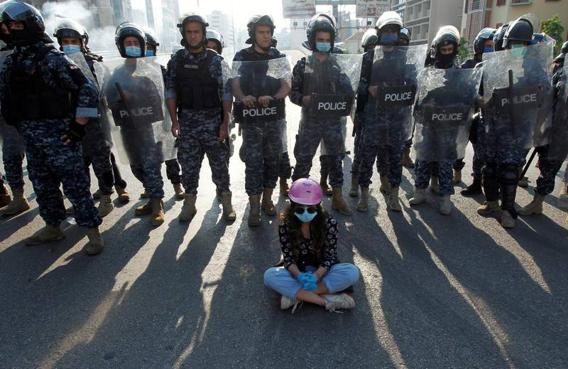 A demonstrator sits on the ground in front of Lebanese police officers during a protest against growing economic hardship in Beirut, Lebanon April 28, 2020. REUTERS/Mohamed Azakir     TPX IMAGES OF THE DAY