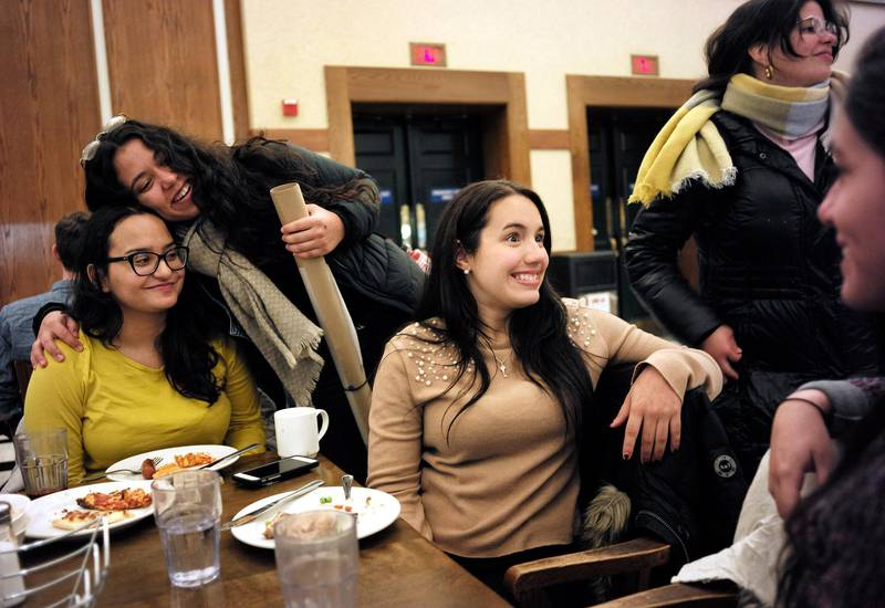 In this Tuesday, Jan. 30, 2018 photo Brown University students from Puerto Rico, Jessica Ortiz, of Gurabo, seated left, receives a hug from Mariana Ramos Ortiz, of Cabo Rojo, top left, as Fabiola Guasp, of San Juan, center, speaks with Coral Murphy, of Manati, right, and Katerina Ramos Jordan, of Trajillo Alto, top right, following dinner in a cafeteria on the school's campus, in Providence, R.I. Dozens of mainland U.S. colleges are offering tuition discounts to help Puerto Rican students continue their studies while the island recovers from Hurricane Maria.  Brown University is among more than a dozen schools that have brought Puerto Rican students to study on campus for free in the wake of September's hurricane.  (AP Photo/Steven Senne)