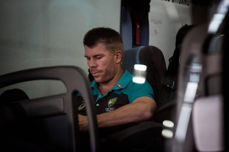 Former vice-captain David Warner of the Australian Cricket Team sits in the shuttle bus as he arrives at OR Tambo International Airport after the team was caught cheating in the Sunfoil Test Series between between Australia and South Africa on March 27, 2018.  / AFP PHOTO / GULSHAN KHAN