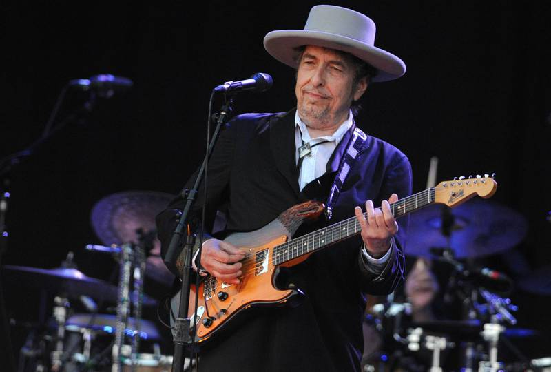 """(FILES) In this file photo taken on July 22, 2012 Bob Dylan performs on stage during the 21st edition of the Vieilles Charrues music festival in Carhaix-Plouguer, western France.  Legendary US folk singer Bob Dylan releases his first album of original songs in eight years on June 19, 2020, with the ten-track """"Rough and Rowdy Ways.""""Dylan's 39th studio album features a 17-minute ballad about the assassination of John F Kennedy, as well as a tribute to American electric bluesman Jimmy Reed.  / AFP / Fred TANNEAU"""