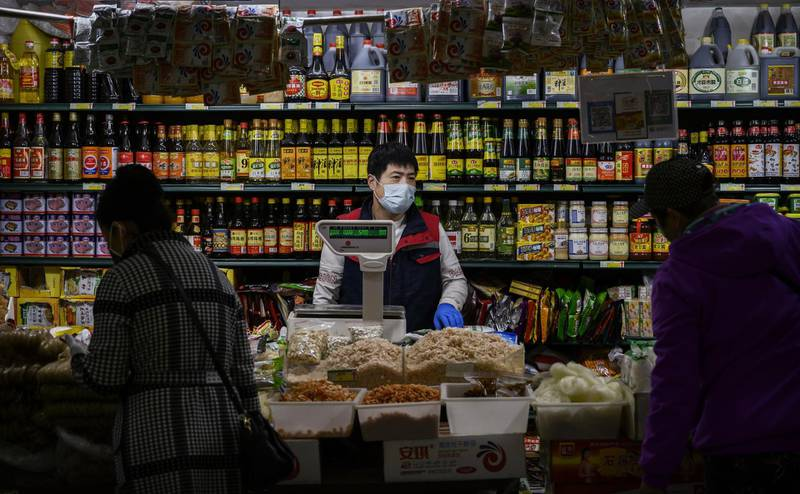BEIJING, CHINA - APRIL 24: A Chinese vendor wears a protective mask as he stands in front of sauces for sale at a food market on April 24, 2020 in Beijing, China. After decades of growth, officials said Chinas economy had shrunk in the latest quarter due to the impact of the coronavirus epidemic. The slump in the worlds second largest economy is regarded as a sign of difficult times ahead for the global economy. While industrial sectors in China are showing signs of reviving production, a majority of private companies are operating at only 50% capacity, according to analysts. With the pandemic hitting hard across the world, officially the number of coronavirus cases in China is dwindling, ever since the government imposed sweeping measures to keep the disease from spreading. Officials believe the worst appears to be over in China, though there are concerns of another wave of infections as the government attempts to reboot the worlds second largest economy. Since January, China has recorded more than 81,000 cases of COVID-19 and at least 3200 deaths, mostly in and around the city of Wuhan, in central Hubei province, where the outbreak first started. (Photo by Kevin Frayer/Getty Images)