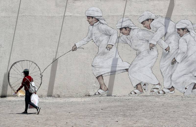 DUBAI, UNITED ARAB EMIRATES , June 11 – 2020 :- A woman wearing face mask and passing by the art work of Emirati boys playing in Al Satwa area in Dubai. (Pawan Singh / The National) For Standalone/Instagram/Big Picture