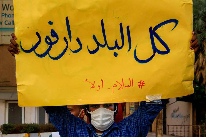 """(FILES) In this file photo taken on July 4, 2020, A mask-clad demonstrator (due to the COVID-19 coronavirus pandemic) stands with a sign reading in Arabic """"all of the country is Darfur, #PeaceFirst"""", during a protest outside the Sudanese Professionals Association in the Garden City district of Sudan's capital Khartoum, in solidarity with the people of the Nertiti region of Central Darfur province in the country's southwest. Ongoing clashes in Sudan's restive Darfur have killed at least 48 people in two days, state media said, just over two weeks after a long-running peacekeeping mission ended operations. The violence has pitted the Massalit tribe against Arab nomads in El Geneina, the capital of West Darfur state, but later morphed into broader fighting involving armed militias in the area. / AFP / ASHRAF SHAZLY"""
