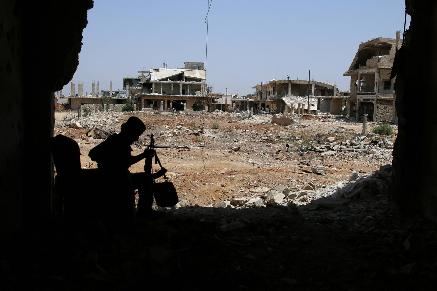 A Free Syrian Army fighter sits with his weapon in al-Manshiyeh neighbourhood in Deraa, Syria July 21, 2017. REUTERS/Alaa Al-Faqir